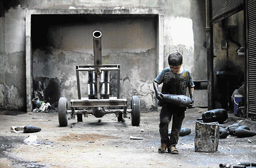 Issa, 10, carries a mortar shell in a weapons factory run by the Free Syrian Army, in Aleppo. Issa works with his father in the factory for 10 hours every day except Fridays