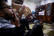 Palestinian refugee family watches a televised broadcast of U.S. President Donald Trump delivering an address where he announced that the United States recognises Jerusalem as the capital of Israel, at Al-Baqaa Palestinian refugee camp, near Amman, Jordan December 6, 2017.