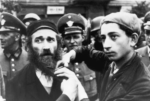 A Jewish boy is forced to cut his father's beard under the watch of soldiers in Nazi Germany. As the Third Reich escalated its persecution of Jews, it assumed the power to decide who was and who wasn't a rightful citizen, based on specific documents that people were expected to produce to prove their heredity.. BETTMANN/GETTY IMAGES