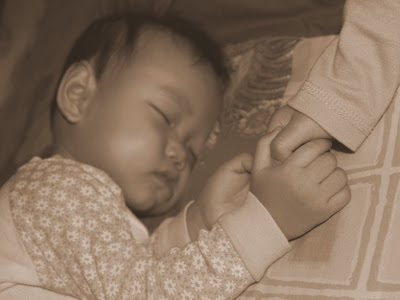 Zaria and Zara holding hands when they slept