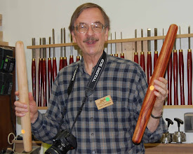 Photo: Gary Guenther shows the similarity of his French style rolling pin and Tim Aley's.  Both did independent internet research and determined this was a popular shape and size.  Gary's is the variegated padauk and Tim's is maple.
