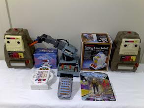 Photo: 2XLs either side, Dingbot, Armatron Robot ARM, TomyTime Talking Tutor Robot, D.A.T.A.M.A.N, Star Trek TNG Data