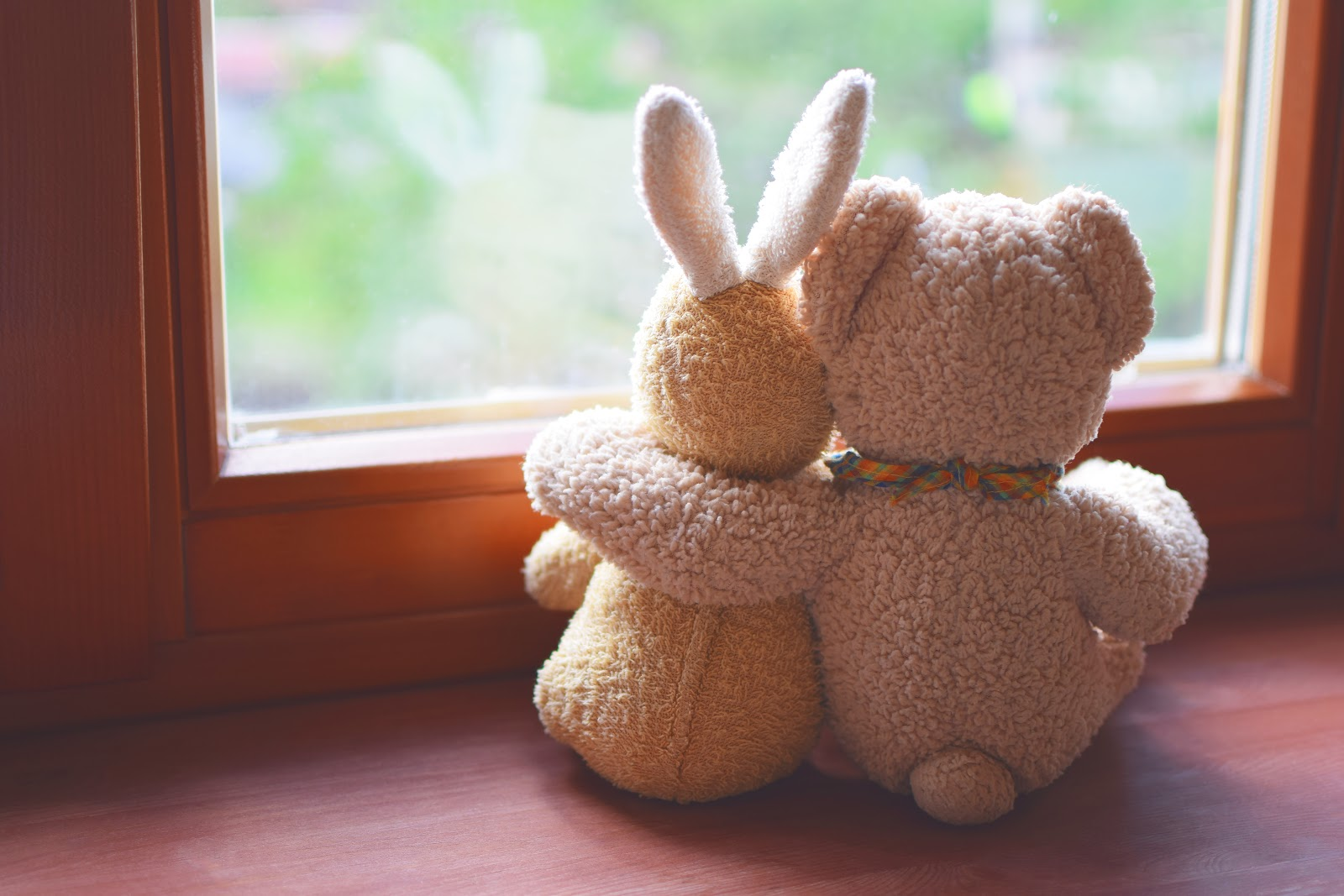 A stuffed bunny and bear with their arms around each other