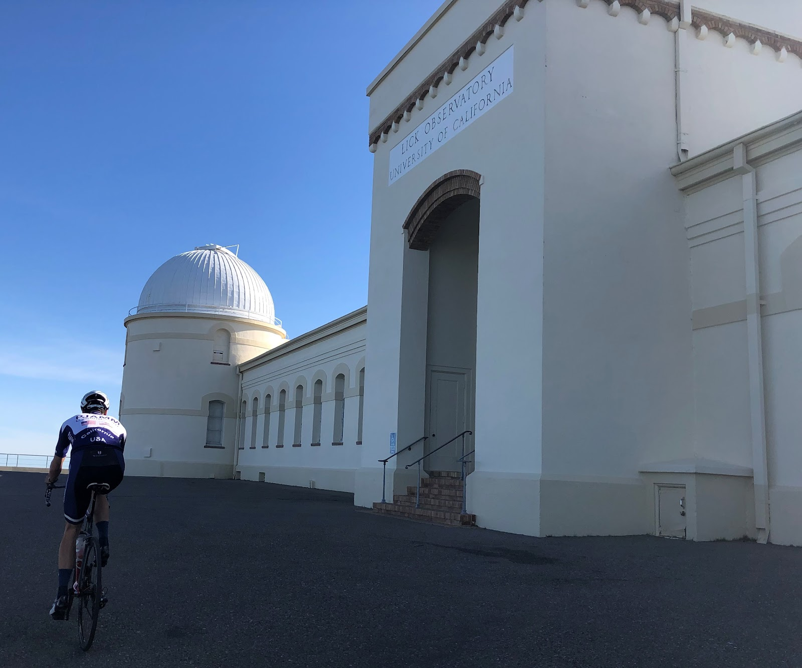Biking Mt. Hamilton West - Lick Observatory entrance. Cyclist riding past front of Lick Observatory.
