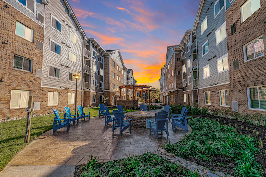 WaterWalk Charlotte - Arrowood outdoor lounge area with chairs and firepit at dusk