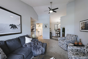 Living room with brown carpet, light gray walls, dark gray couch, and patterned accent chairs