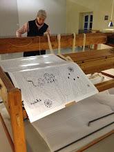 Photo: Mme Dassonval, préparant les lisses et le futur carton à tisser sur le métier