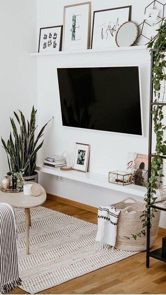 Sala com TV, paredes e painel de TV brancos, objetos decorativos, vasos de planta e mesa de centro.