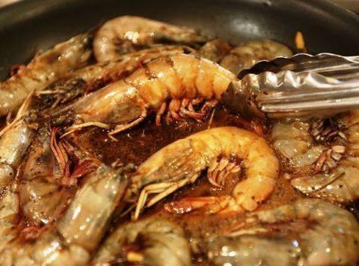 In a large heavy skillet, preferably cast iron, combine shrimp, lemon juice, garlic, lemon...