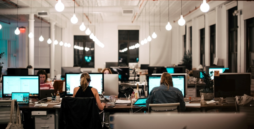 employees working at their desks in an office with an open floor plan