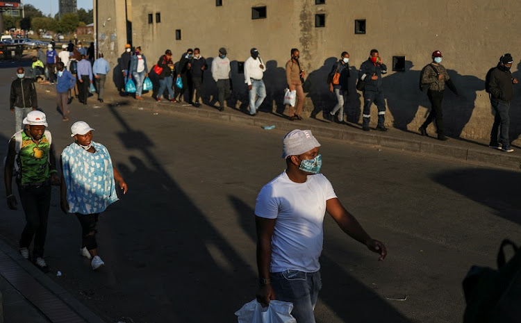 Locals, some wearing protective masks, are seen returning from work, as South Africa starts to relax some aspects of a stringent nationwide coronavirus disease (COVID-19) lockdown, in Soweto, South Africa, May 11, 2020.