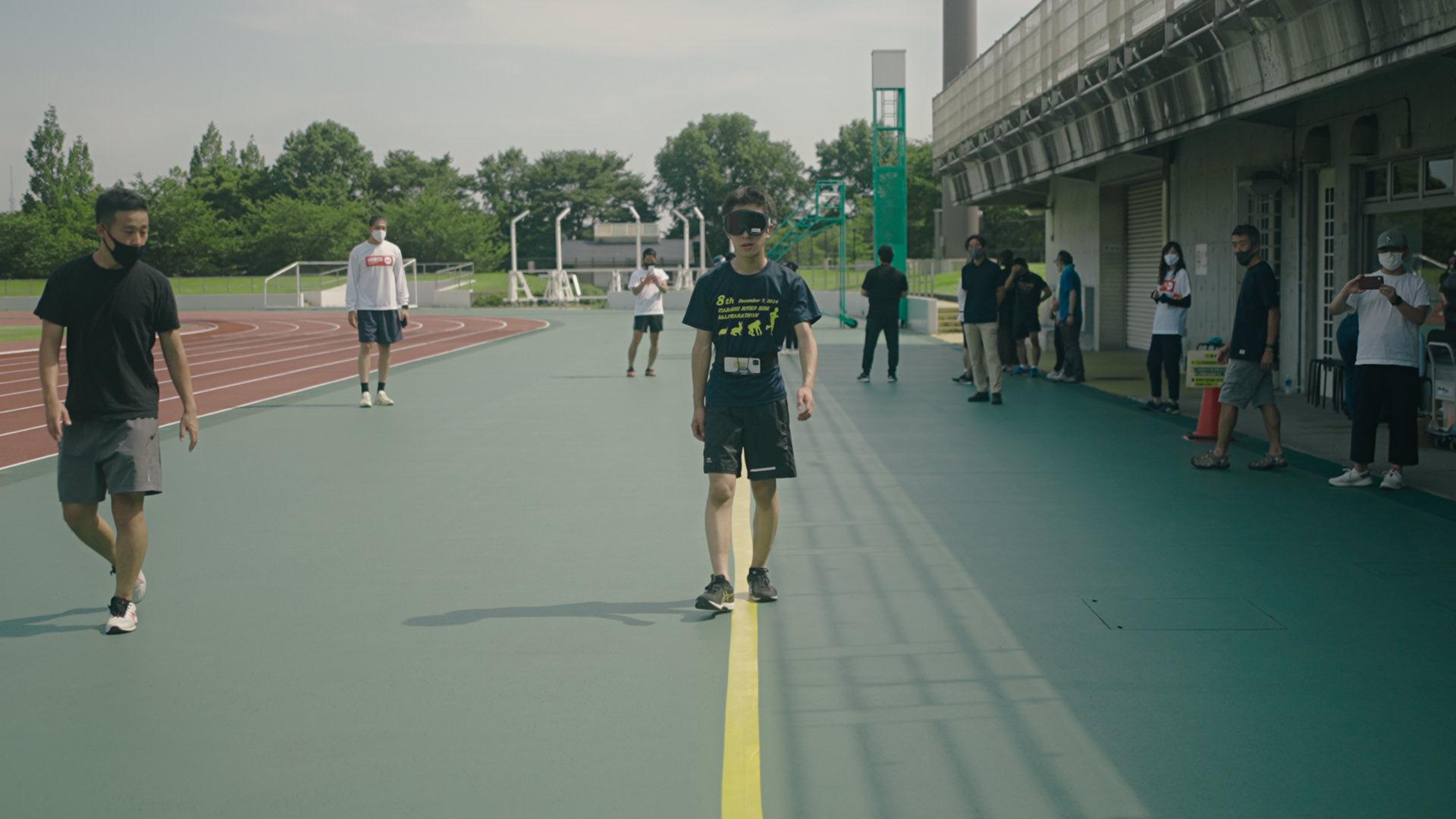 写真:アプリの挙動を確認しながらコース上を歩くアイマスクをした高校生の男性のテスト走者。