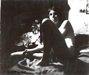 ietwat onscherpe foto van een naakte vrouw, zittend op een bed