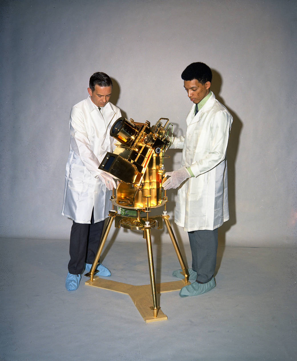 Dr. George Carruthers at right and William Conway with small gold-plated science instrument on tripod