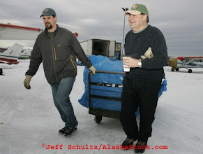 Photo: Saturday, Feb. 18, 2006  Anchorage, Alaska. Volunteer Iditarod Airforce pilots and others load straw into Cessna planes headed out to checkpoints along the trail.  Each musher is given one bale of straw at a checkpoint to bed their dogs down.
