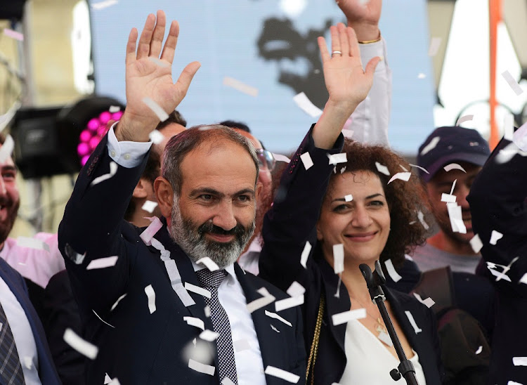 Newly elected Prime Minister of Armenia Nikol Pashinyan, left, greets supporters during a meeting in Republic Square in Yerevan, Armenia, on May 8 2018. Picture: REUTERS