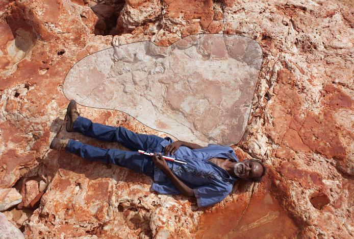 A supplied image of Aboriginal elder and Goolarabooloo Law Boss Richard Hunter alongside a 1.75m sauropod dinosaur track in the Lower Cretaceous Broome Sandstone, Walmadany area, Dampier Peninsula, in Western Australia. Picture via REUTERS