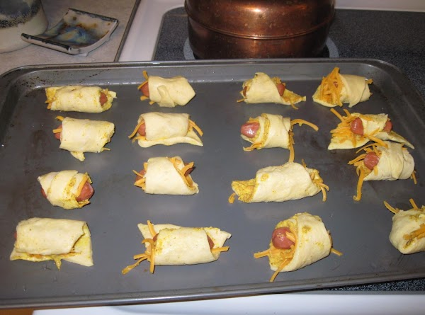 Cut each triangle in half, sprinkle with a bit of cheese, add a sausage...
