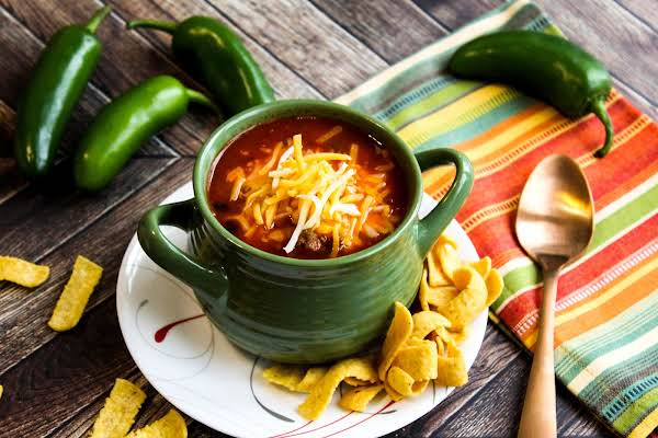A Bowl Of Chili With Shredded Cheese On Top.