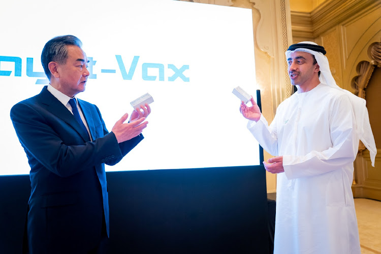 China's foreign minister Wang Yi and his UAE counterpart Abdullah Bin Zayed Al Nahyan show the Chinese-made Sinopharm vaccine, in Abu Dhabi, United Arab Emirates, March 28 2021. Picture: WAM/HANDOUT/REUTERS