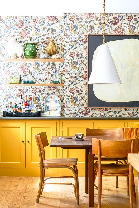 dining room with yellow cabinets and wallpaper