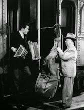 """Photo: O """"Cameo"""" de Hitchcock em Pacto Sinistro, carregando um """"double bass"""" (Contrabaixo)"""