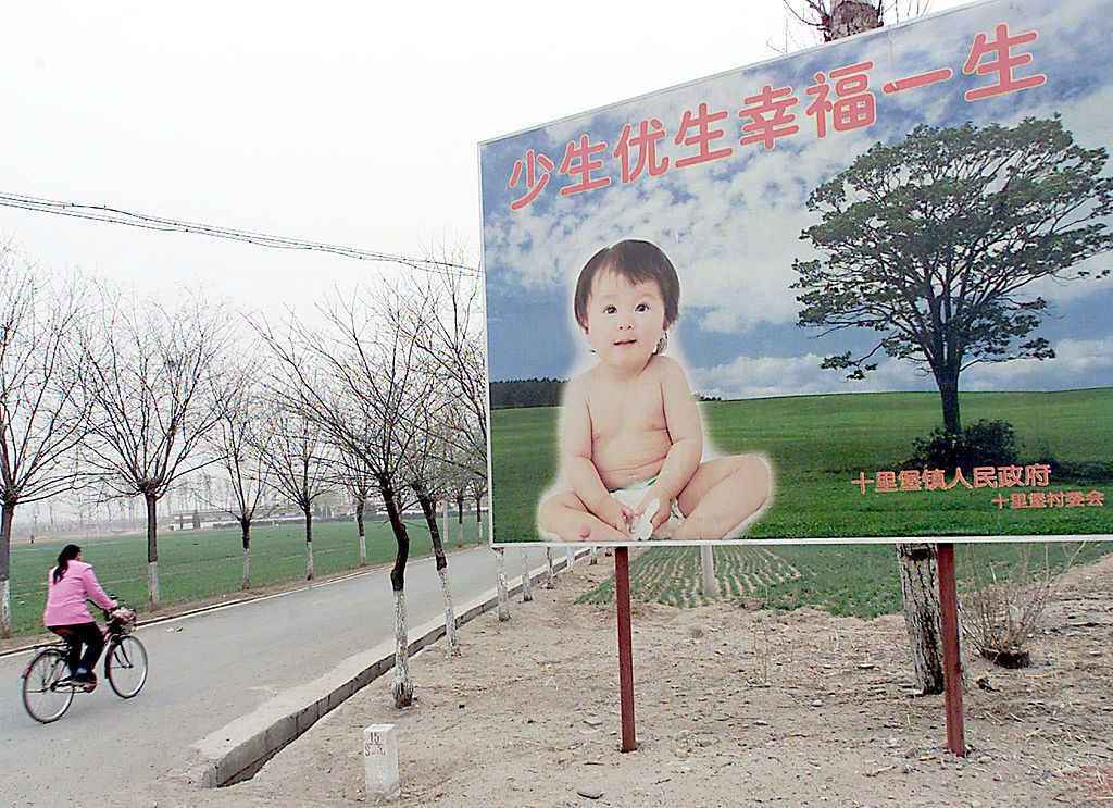 A woman cycles past a billboard encouraging couples to have only one child, along a road leading to a village in the suburb of Beijing, 25 March 2001. The CCP's much-decried One Child Policy has had serious economic and social consequences for the country. Even a relaxation to a two and three child policy has not rectified China's population crisis.