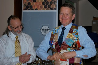 Photo: INIB Chairman, Michael Young MBE presenting a hand made beekeepers waistcoat to Bill Turnbull, INIB President.