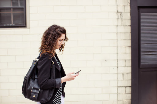 smartly dressed woman walking down the street using a mobile phone