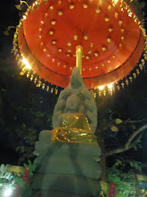 Photo: Buddha (in gold toga) sitting in the garden, under an umbrella-like thing (keeping the statue clean) but he is protected/surrounded by a 7-headed snake. This picture is taken a night, hence the lights on the umbrella.