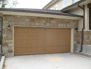 """Photo: This is a door with a more contemporay finish. This door is 16' wide by 7"""" tall. It is shown here prior to the Faux finish it will recieve. This is a factory primed door."""
