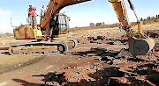 A hijacked grouser-padded excavator  digs up  a tarred road  near the N12 highway between Klerksdorp and Potchefstroom.
