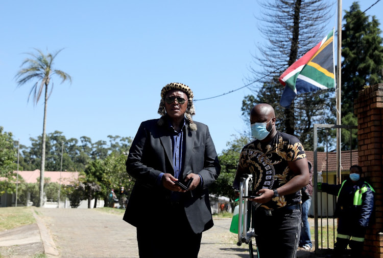 The SA flag is flown half mast at King Goodwill Zwelithini Zulu's KwaKhethomthandayo Royal Palace where hundreds of people have been making their way in and out to mourn the passing of the king. Pictured is the king's younger brother Prince Mbonisi Zulu outside the palace.
