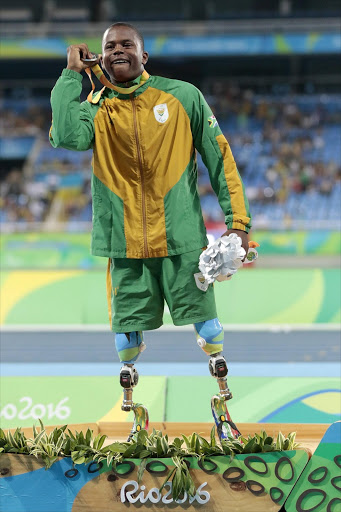 Silver medalist Ntando Mahlangu of South Africa celebrate on the podium at the medal ceremony for the Menâs 200m â T42 Final during day 4 of the Rio 2016 Paralympic Games at the Olympic Stadium on September 11, 2016 in Rio de Janeiro, Brazil. (Photo by Alexandre Loureiro/Getty Images)