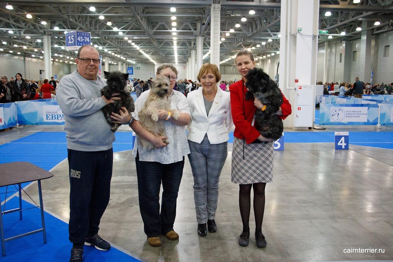 Фото керн терьеров питомника Еливс победителей с владельцами, хендлером и экспертом на призовом месте выставки.