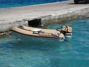 Photo: Tan Sunbrella & brown Naugehyde reinforcement, notice outboard is also covered, and registration numbers appear to be painted on...