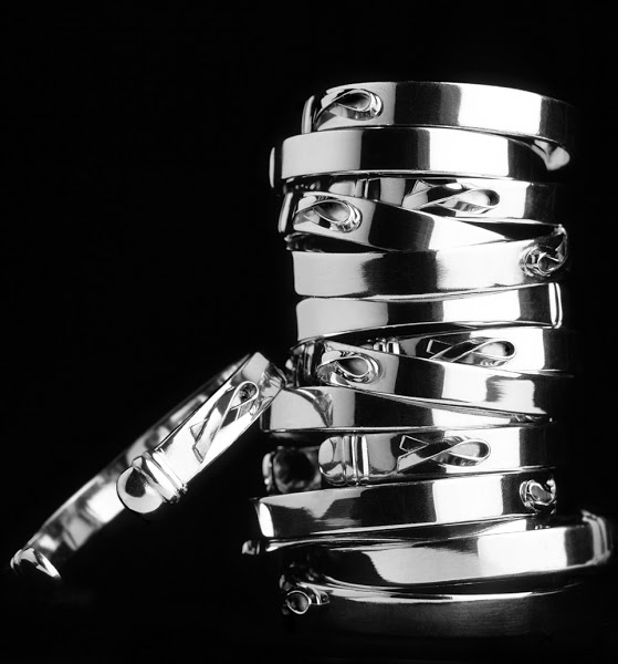 """Photo: Cuff Style Bracelets The Bracelet is a 1/4-inch wide, cuff-shaped band featuring the familiar small, raised AIDS ribbon on the outside. Inside is a small plaque inscribed with """"Until There's A Cure."""" Designed by Isabella Geddes da Filicaia and manufactured in Italy.  Available in 4 metals/price-points: Silver-plate: $25 Stainless Steel: $50 Sterling Silver: $95 Sterling Silver w/ 18kt Gold Ribbon: $125"""