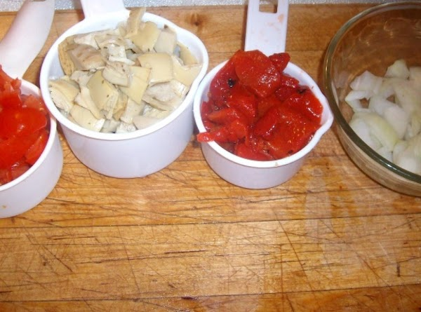 Chop artichokes, tomatoes, roasted red bell peppers, & onion. After chopping, put in small...