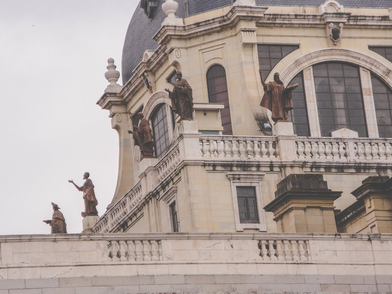 A set of statues at the top of a building