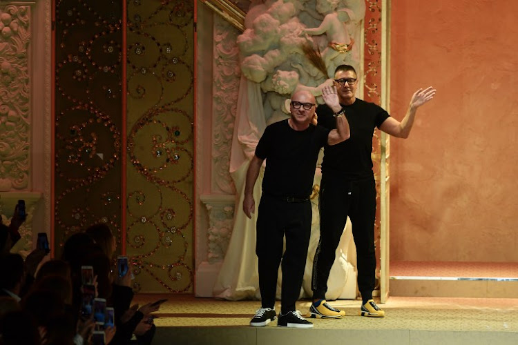 Italian fashion designers Domenico Dolce and Stefano Gabbana acknowledge the audience at the end of their women's Autumn/Winter 2018/2019 fashion show in Milan on February 25 2018.