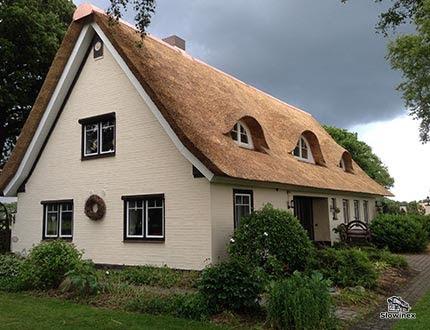 Domek ze spadzistym dachem trzcinowym z fasadą w kolorze kremowym w otoczeniu zieleni i pochmurnego nieba