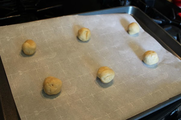 Using one tablespoon of dough for each cookie, roll into balls. Place on greased...