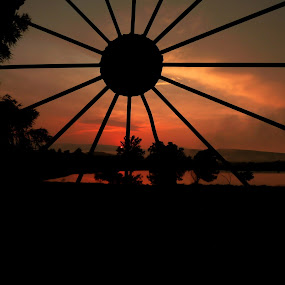 Through the Wagon Wheel by Sandra Millsap - Landscapes Waterscapes ( water, sunset, silhouette, wagon wheel, pond )