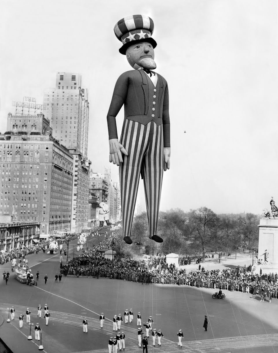 Float handlers control the balloon strings of an Uncle Sam float in the Macy's Day parade