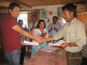 Photo: COMMITTED member Jayjeev Hada and school staff, Kumar Basnet shake hands to setting up  the fishery.