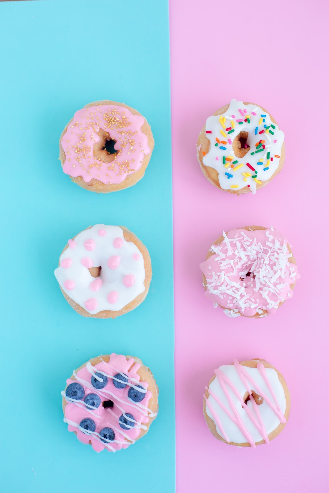 Donuts with different colored icing and sprinkles with a blue and pink background