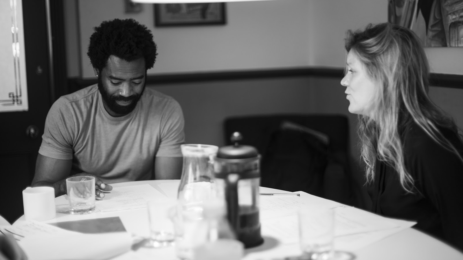 Black and white still from 'Candice' (2017). Greg and Candice sit beside each other at a restaurant table. Greg looks down at the menu, whilst Candice looks across the table at him, speaking.