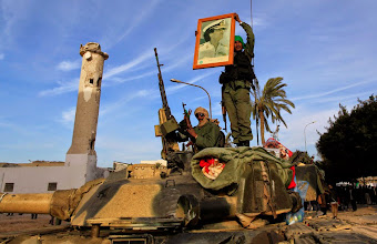Photo: A Libyan army soldier holds a picture of leader Muammar Gaddafi near a destroyed mosque at Martyr's Square in the centre of Zawiyah, 50 km (30 miles) west of the capital Tripoli, March 11, 2011. REUTERS/Ahmed Jadallah (LIBYA - Tags: POLITICS CIVIL UNREST IMAGES OF THE DAY)