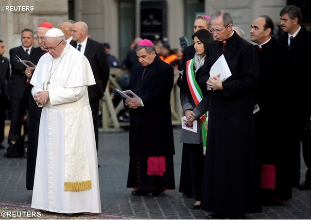 Pope Francis prays during the Immaculate Conception celebration in Piazza di Spagna in Rome, flanked by Rome's mayor, Virginia Raggi (R) - REUTERS