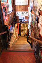 """Photo: Domingo de libros, domingo de Ruta Librera  Hoy viajamos a San Francisco, una ciudad íntimamente ligada a la literatura, cuna de muchos autores pertenecientes a la generación beat que, a partir de los años 50 actuó como un imán para un gran grupo de artistas, músicos y escritores. En esta ciudad precisamente, en Columbus Avenue, encontramos un edificio triangular cuya visita es imprescindible. Se trata de City Lights Booksellers & Publishers.  Fundada en 1953 por el poeta Lawrence Ferlinghetti y Peter D. Martin, esta librería es uno de los grandes referentes en Estados Unidos cuando se habla de librerías independientes. Con un catálogo que ha crecido año tras año y una intensa actividad cultural, mantiene el espíritu beat, como puede apreciarse en esas grandes pancartas con mensajes cambiantes que ya son un clásico de San Francisco. Con el tiempo, se han constituido también como editorial, y van editando libros de todos los géneros que ahora ocupan un lugar entre sus muchos, muchos estantes. Una librería que ya se ha convertido en un punto de encuentro para los amantes de las letras, y cuya fachada también es un reclamo turístico de quienes quieren conocer las luces de la ciudad. La literatura ilumina las mentes, no cabe duda, y en esta podemos encontrar cualquier cosa que busquemos. Solo que corremos el riesgo de no querer salir.  Una librería con mucha historia. Si las paredes hablaran... contarían la historia del sótano de este lugar. Descubierto por casualidad por el propietario, que se encontró con un taller utilizado como almacén por un electricista chino, o como guarida del dragón ceremonial del Año Nuevo Chino durante mucho tiempo (de hecho el propio Ferlinghetti habla de ello en uno de sus poemas). O tal vez, nos contara la historia de cuando se convirtió en una bodega literaria en la que se podían consumir libros o un tablón usado como una surte de """"correo literario"""" por la que pasaron muchos, muchos grandes nombres. Si las paredes hablaran... nos r"""